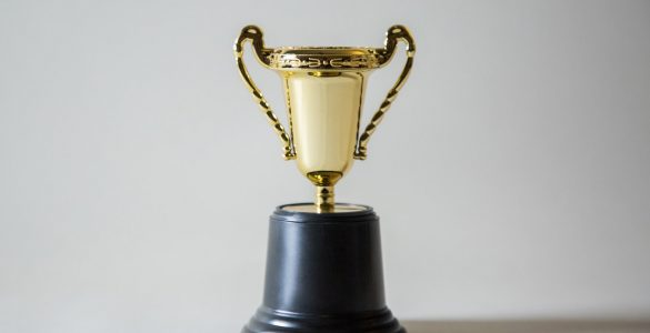 A gold trophy with a black base